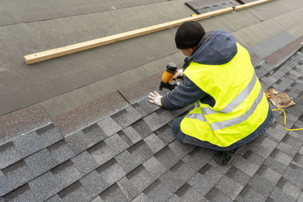 Qualified workman in uniform work wear using air or pneumatic nail gun and installing asphalt or bitumen shingle on top of the new roof under construction residential building